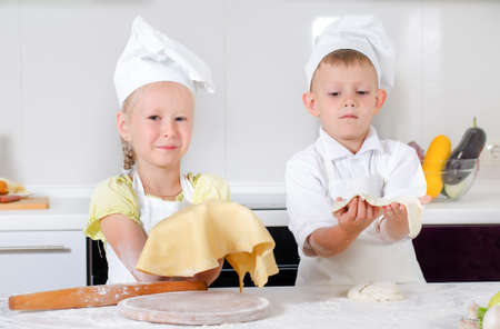 pizza base: Smiling pleased little girl dressed in an apron and chefs cap holding up her thinly rolled out pastry for a pizza base with a proud smile watched by her young brother