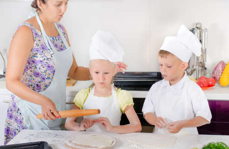 pizza base: Mother teaching two young children, a girl and boy dressed in white chefs uniforms with aprons and toques, to bake in the kitchen showing them how to roll out dough for a homemade pizza base
