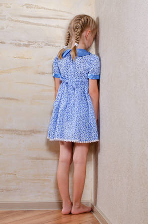 Little girl with her blond hair in braids standing in the corner facing the wall sulking or in punishment for a wrongdoing Stockfoto