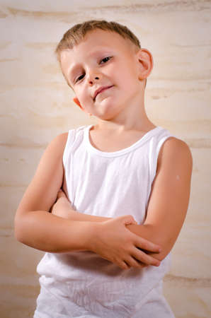 disciplined: Cute boy with a nasty facial expression looking at camera while wearing a white A-shirt and posing with folded arms, indoors portrait Stock Photo