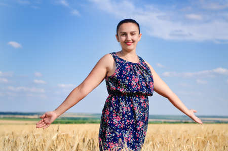 Attractive woman wearing sunglasses and a summer top standing enjoying the sun in a wheat field with her arms outstretched and head tilted to the sun with a smile photo