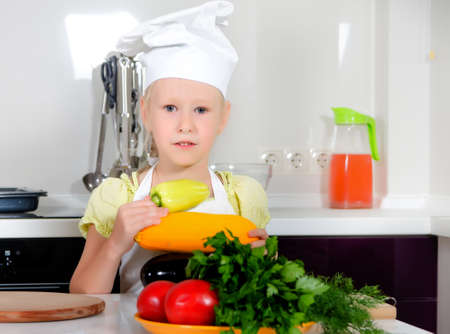 be dressed in: Cute little girl learning to be a chef standing with an assortment of farm fresh vegetables in the kitchen dressed in a white toque and apron