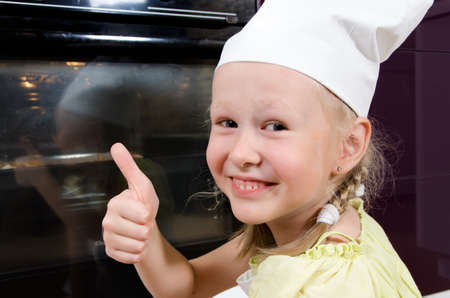 crouches: Cute happy young girl in a toque giving a thumbs up gesture of success as she crouches down alongside the oven watching a pizza bake that she has just prepared herself