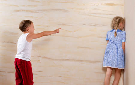 Two Cute White Kids Playing Hide and Seek Isolated on Light Brown Wooden Walls photo