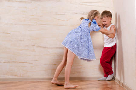 celos: El muchacho y la muchacha de los niños que juegan en el hogar, aislado en paredes de madera