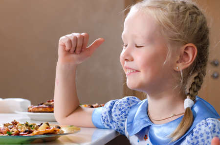 Pretty little girl sitting at the dinner table eating homemade pizza wiping her mouth with a napkin while turning to glance at the camera with a serious expression photo