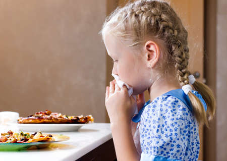 turning table: Pretty little girl sitting at the dinner table eating homemade pizza wiping her mouth with a napkin while turning to glance at the camera with a serious expression