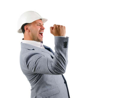 jubilation: Man wearing a hardhat cheering in jubilation and punching the air with his fist as he celebrates a success, conceptual of a builder, architect or engineer Stock Photo