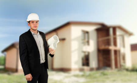trustful: Architect, builder or structural engineer wearing a hardhat standing with folded arms in front of a newly constructed house Stock Photo