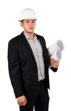 若い男性建築家またはエンジニア青写真と一緒に立っているヘルメットを身に着けている白の真剣な表情でカメラを見て彼の腕の下重ね