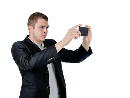 Serious attractive young man in and suit taking a photograph using his mobile phone, isolated on white photo