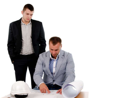 Architect sitting working on building plans with the blue print unrolled in font of him and his hardhat alongside watched by a colleague in a suit photo
