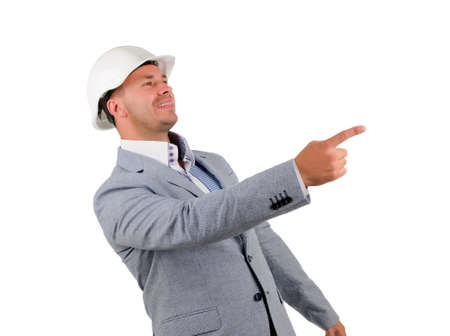 Happy Middle Age Engineer in Gray Coat and White Helmet Pointing Side. Isolated on White Background. photo