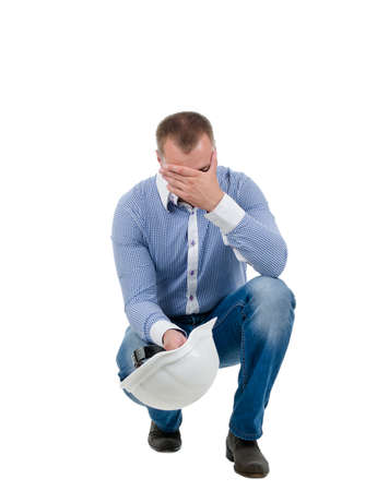 Worried engineer bending down in a crouch with his hardhat in his hand holding his head, isolated on white