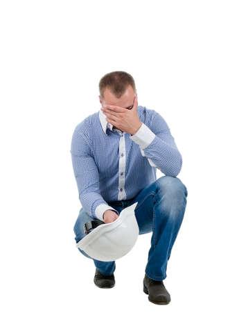 bending down: Ingeniero Preocupado agacharse en cuclillas con su casco en la mano sosteniendo su cabeza, aislado en blanco