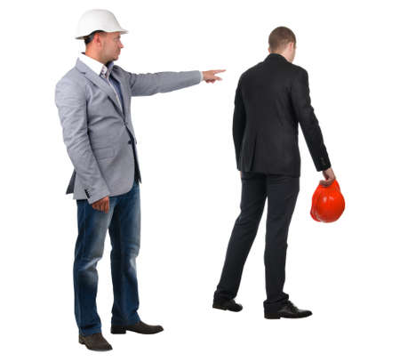 Architect , builder or engineer admonishing his young partner pointing the finger of blame at him as he turns away dejectedly