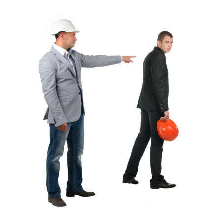 abject: Architect , builder or engineer admonishing his young partner pointing the finger of blame at him as he turns away dejectedly