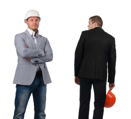 abject: Man with Hard Hat Skulking Past Confident Colleague with Arms Crossed
