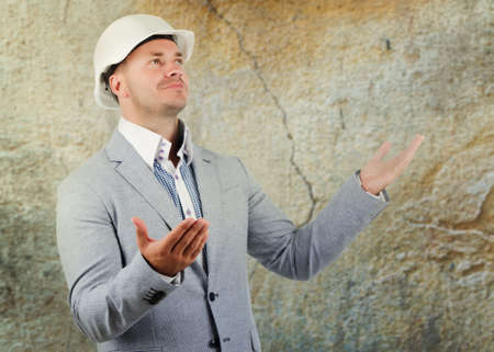 ignorance: Structural engineer pleading ignorance or a large crack in a wall alongside him raising his hands to show he does not know what happened