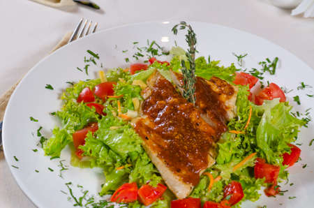 mouth watering: Close up Delicious Recipe on Frisee Lettuce on White Round Plate with Utensils on Sides.