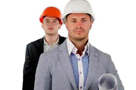 Successful foreman or supervisor of a construction team in his hardhat with a blueprint under his arm and a team member behind him, on white photo