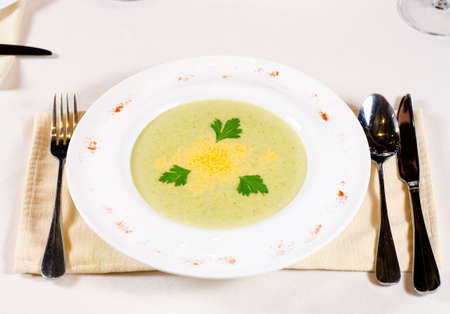plating: Artistic plating of delicious vegetable soup served in a bowl at table garnish with coriander leaves