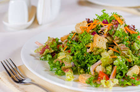 accompaniment: Delicious mixed leafy green lettuce and herb salad with fried crunchy croutons served on a plate at table as a vegetarian main course or accompaniment