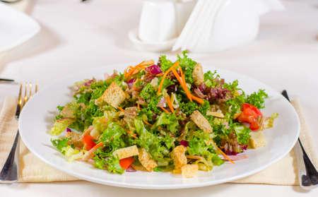 accompagnement: D�licieux feuillue mixte vert laitue et herbes salade avec des cro�tons frits croustillants servi sur un plateau � table comme un cours ou d'accompagnement principal v�g�tarien