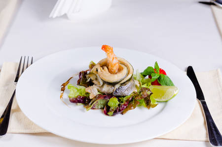 plating: Delicious Main Dish of Fish and Shrimp Meat and Veggies Combination in Stylish Plating on White Round Plate with Fork and Knife on Sides.