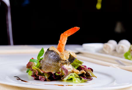 Tasty Main Dish of Rolled Fish Meat on Shrimp with Fresh Leafy Vegetables and Lemon on White Round Plate. Served on the Table at the Restaurant