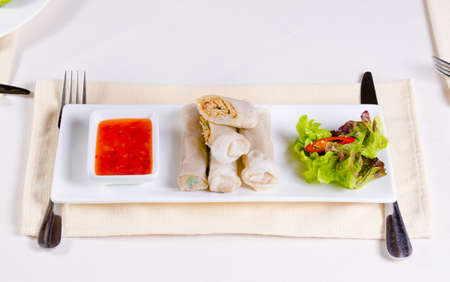 mouth watering: Gourmet Mouth Watering Healthy Spring Rolls Recipe with Fresh Lettuce Vegetable and Sweet Chili Dipping Sauce on White Rectangular Plate.