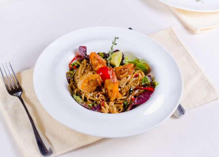 speciality: Speciality pasta recipe with grilled shrimps or prawns, fresh herbs and vegetables garnished with lime served at table