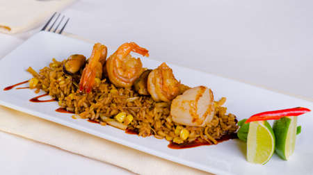 mouth watering: Mouth Watering Main Dish Lemony Risotto with Shrimps on Top. Prepared on White Rectangular Plate, Dine in White Table