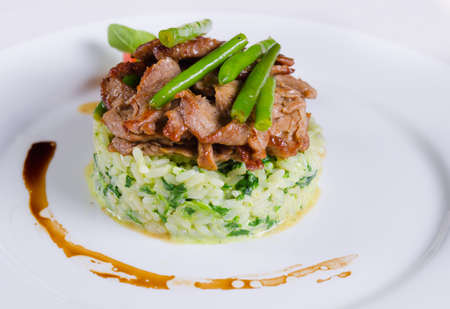 plating: Gourmet Tasty Well- Cooked Beef Meat and Green Beans on Risotto Main Dish. Prepared on White Round Plate with Utensils on Sides.