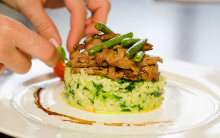 plating: Hands of a chef preparing a plating of thinly sliced marinated grilled beef topped with fresh green beans on savory rice