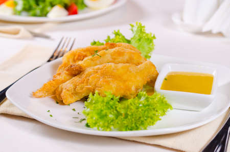 Close Up of Chicken Strips with Mustard Dipping Sauce on White Plate photo