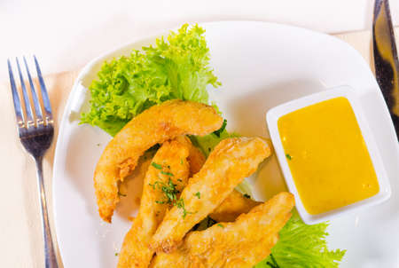 High Angle View of Chicken Strips with Mustard Dipping Sauce on White Plate photo