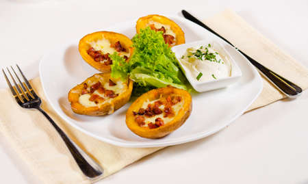 skins: High Angle View of Potato Skins Appetizer with Dipping Sauce Served in Restaurant
