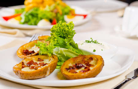 skins: Potato Skins Appetizer with Garnish Served on Plate in Restaurant