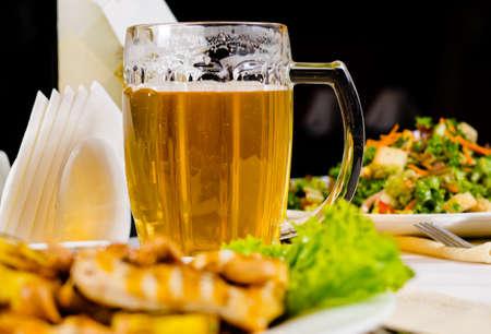 Close-up van de Mok van het bier op restaurant tafel met geïllustreerde eten