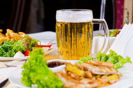 Mug of Beer on Restaurant Table with Plated Food Dishes photo
