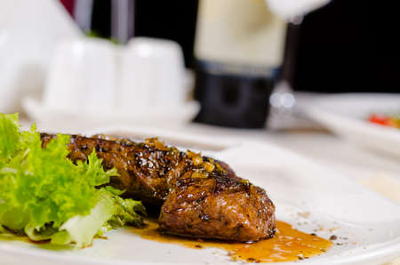 mouth watering: Close up Mouth Watering Juicy Roasted Steak Main Entree with Lettuce on White Plate