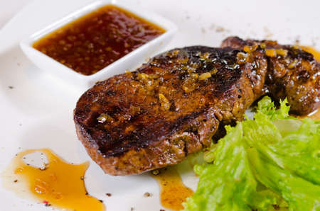 Close up Gourmet Tasty Juicy Grilled Steak Main Dish with Hot Chili Sauce and Fresh Lettuce on White Plate.