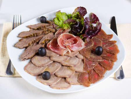 carnes y verduras: Gourmet plato frío de carne en un buffet con carnes ahumadas y procesadas surtidos con guarnición de lechuga y aceitunas frescas, opinión de alto ángulo Foto de archivo