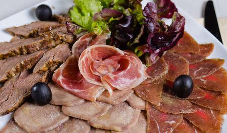 carnes y verduras: Surtido de plato de carne fría artísticamente arreglados con variedades de carne cocida, jamón prosciutto, lechuga y aceitunas