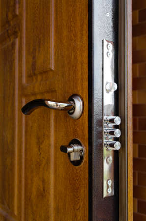 Triple cylinders on a new high security lock installed in a wooden front door to a home with the locks extended