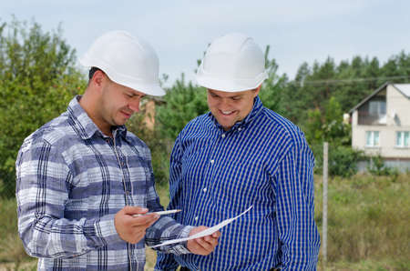 building site: Architect and engineer having a discussion referring to a paper document as they stand on a building site in their hardhats Stock Photo