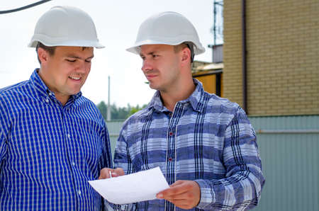 Two builders or engineers in their hardhats standing discussing paperwork and making notes outdoors on a building site