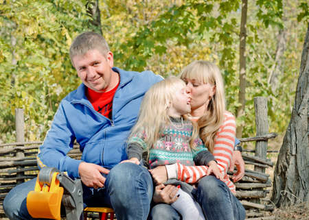 cuddled: Happy young family relaxing outdoors with the father sitting on his daughters toy truck as she leans on his knee cuddled by the attractive blond mother in a leafy garden or woodland Stock Photo