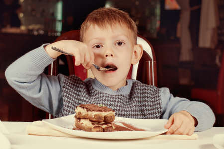 devouring: Little boy licking his fingers in appreciation of the tasty home baked slice of cake he is eating for dessert at the dining table